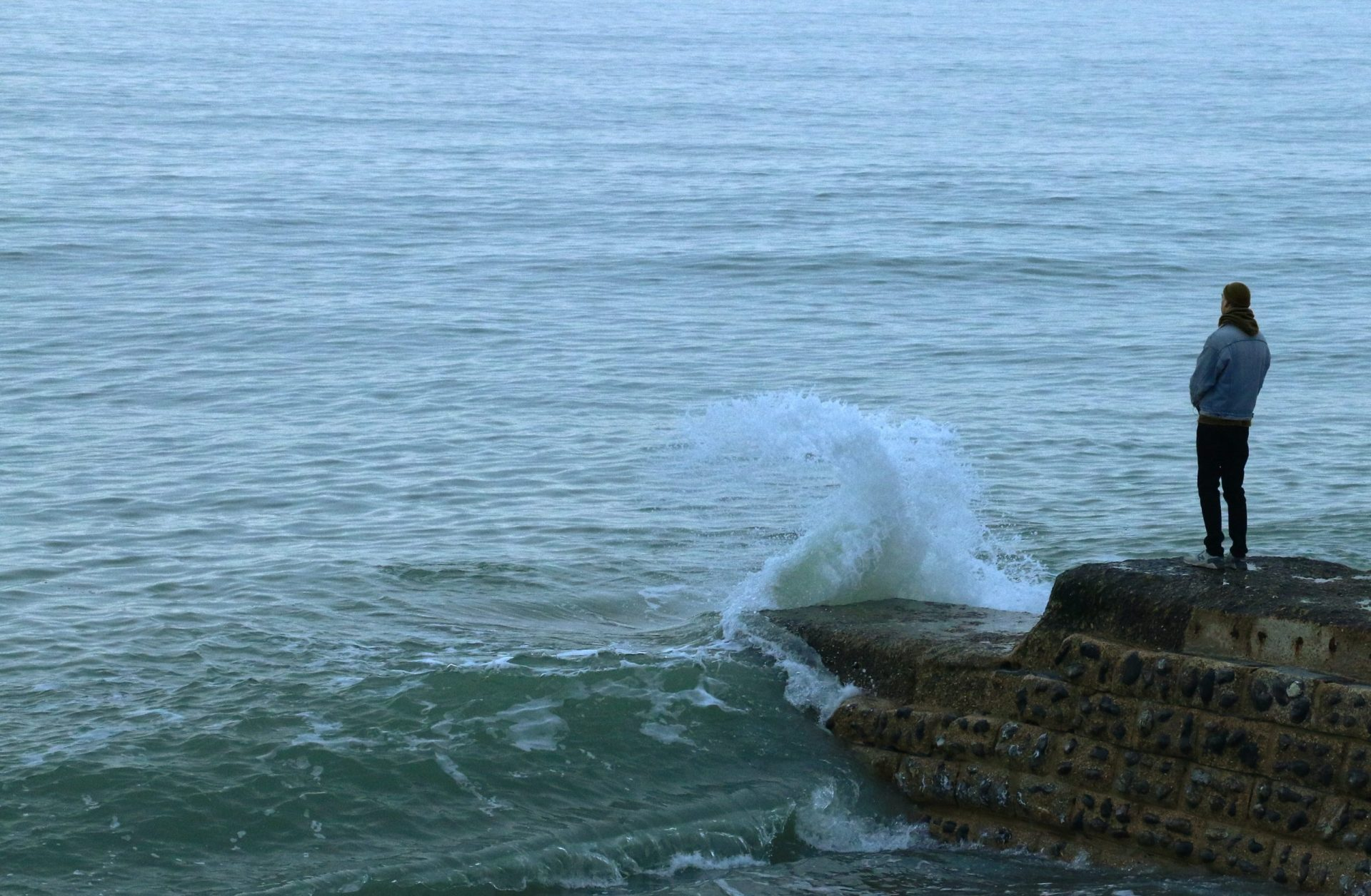 Man standing at the ocean watching waves crash. Representing PTSD Therapy