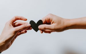 Two hands holding a paper heart. Representing couples therapy.