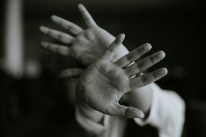 Black and white photo of two hands in front of face. Representing sexual abuse counselling.