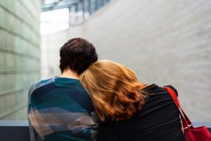 A woman leaning her head on a man's shoulder. Representing trauma counselling.