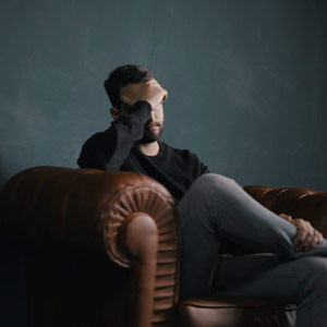 Man sitting on couch with hand over face to represent individual counseling.