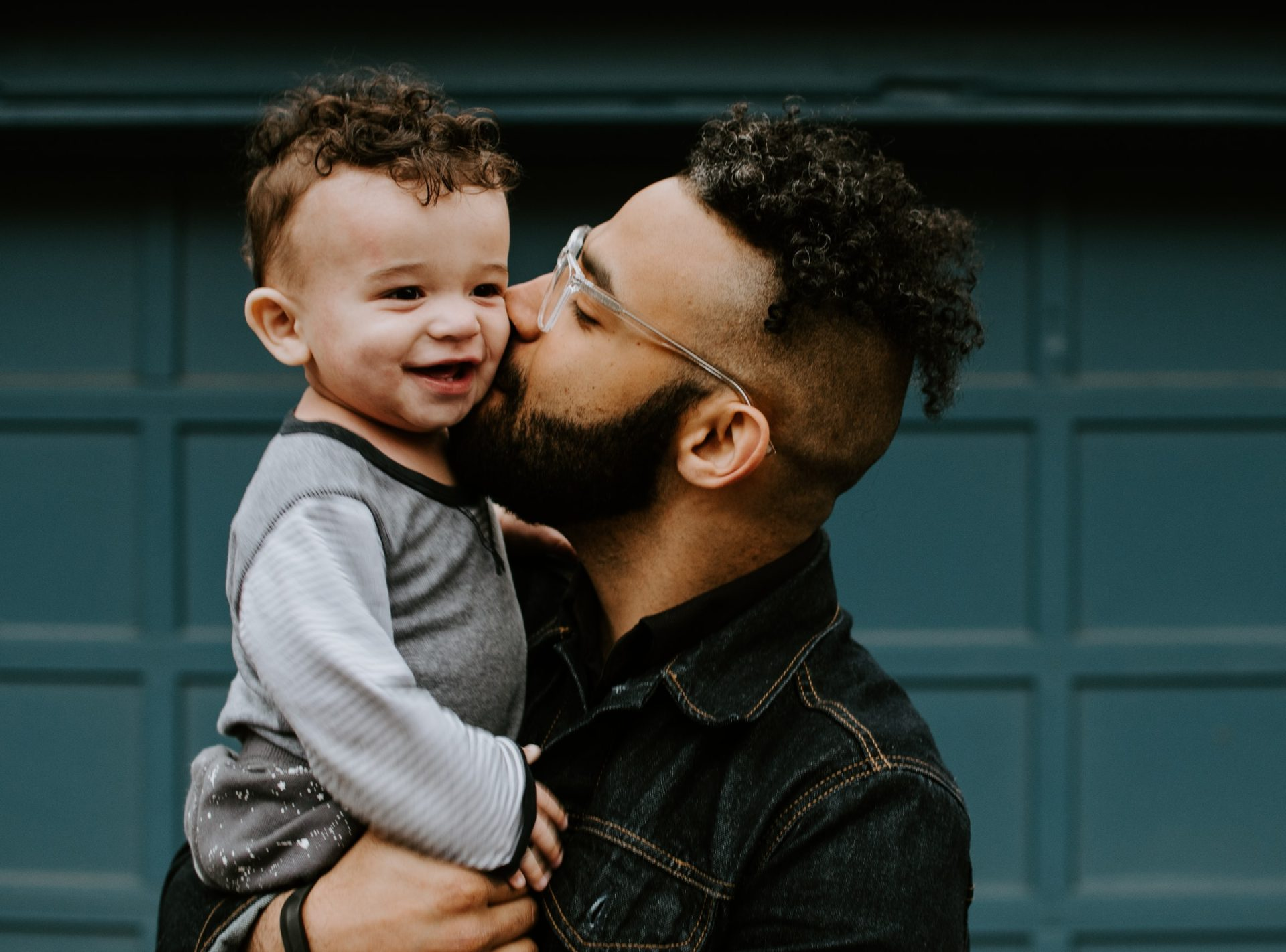 Man holding his son and kissing him on the cheek to represent counseling exercises and parenting with empathy.
