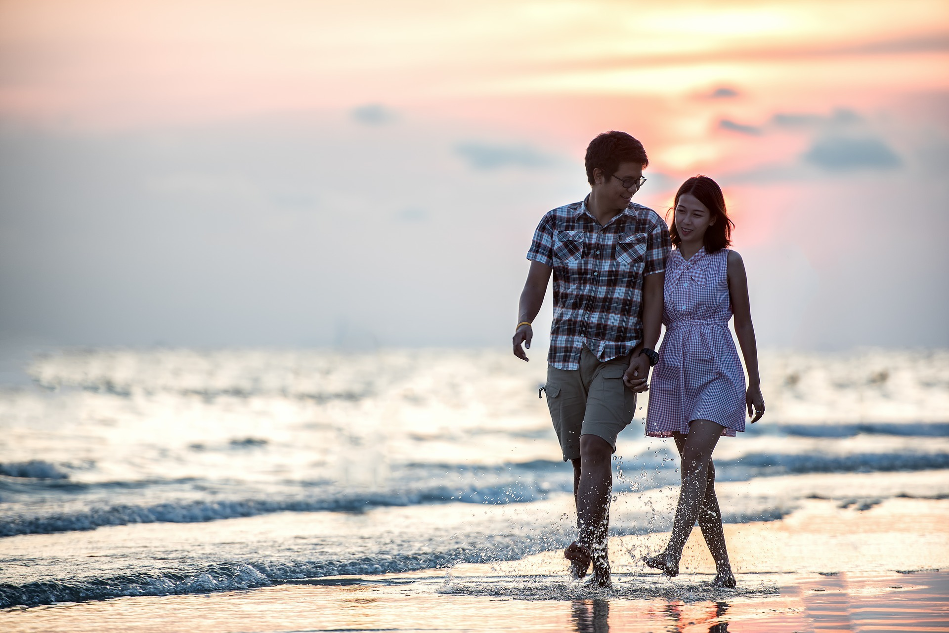 Couple walking on the beach at sunset to represent couples therapy exercises.