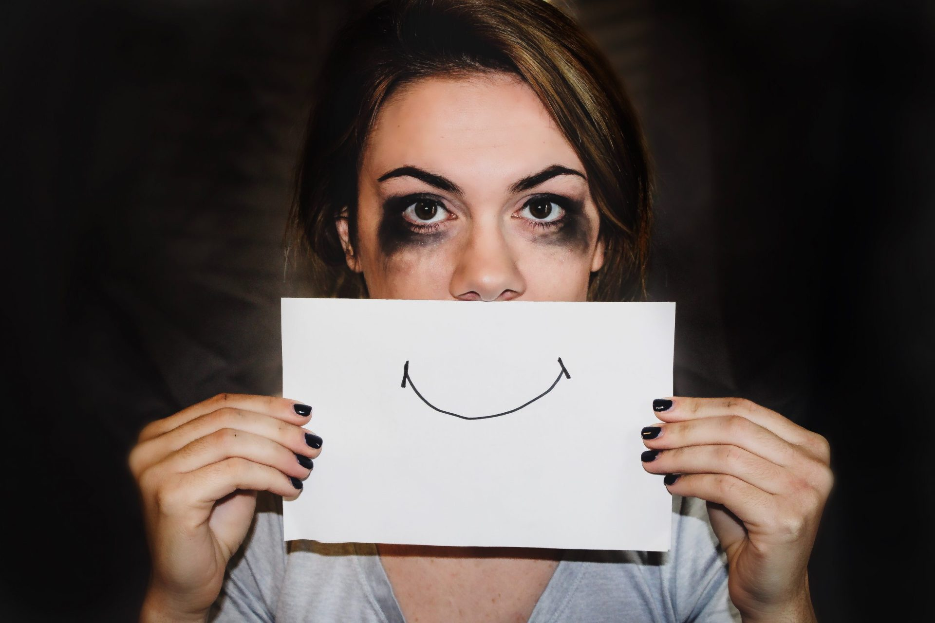 Depression counseling. Upset woman with drawing of smile in front of her face.