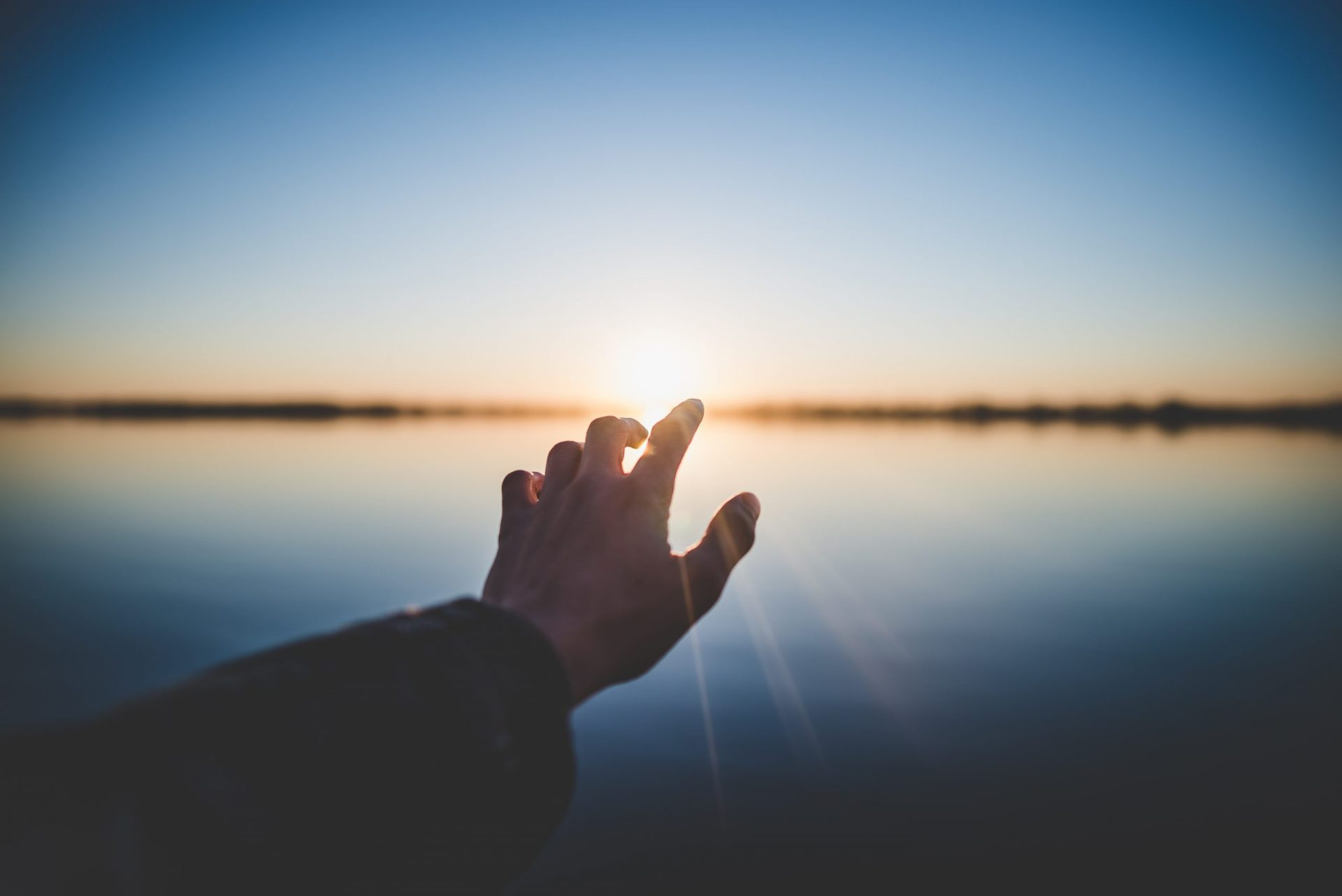 Hand reaching out to sunset over water. Representing panic attach treatment